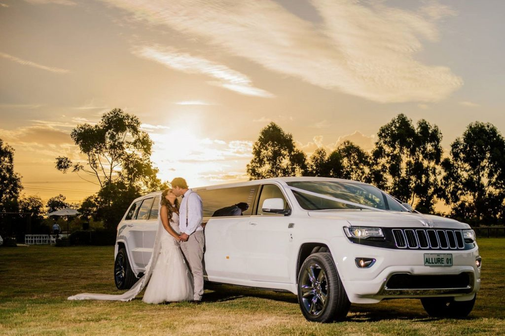 wedding limo - wedding limousine - wedding under the sun - wedding couple in front of a white limousine