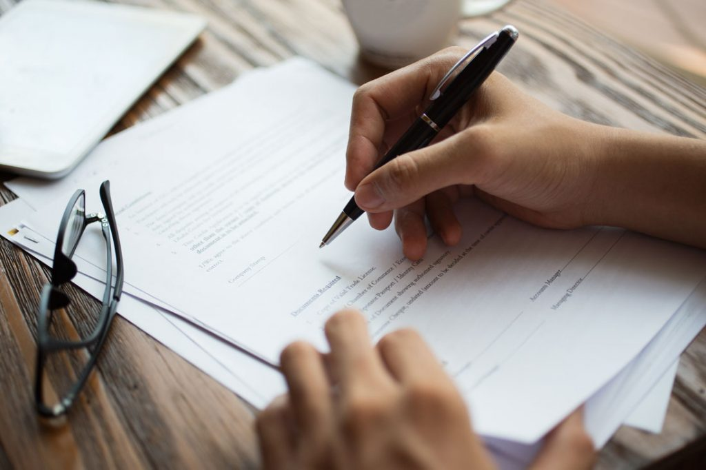 businessman examining papers - signing the insurance contract - insuranec